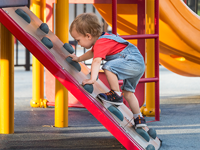 Little boy climing a playground structure-feature