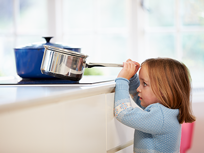 little girl grabbing pot on stove