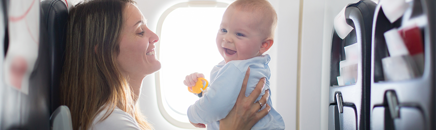 mom playing with baby on airplane