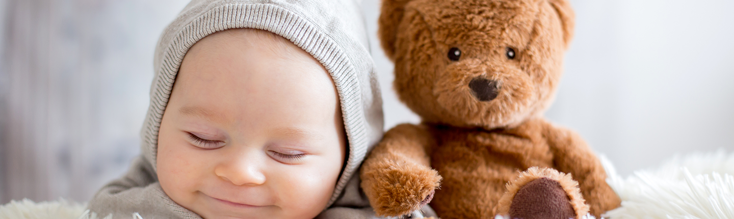 baby boy sleeping in bed with teddy bear