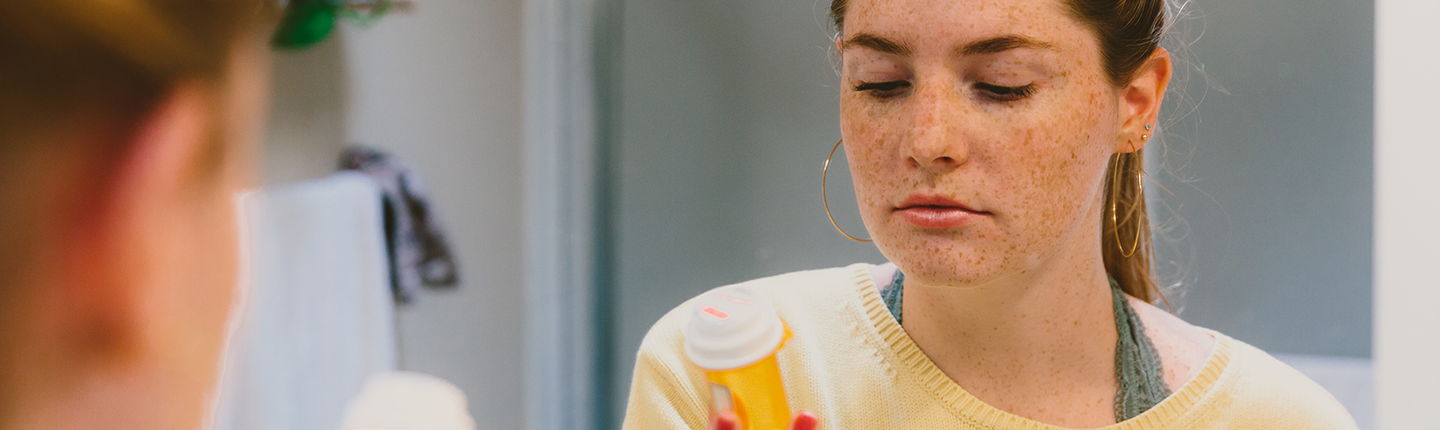 girl looking at pill bottle