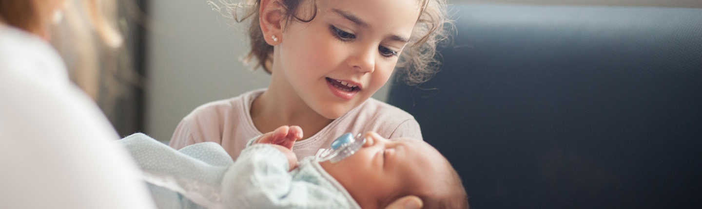 little girl holding newborn baby