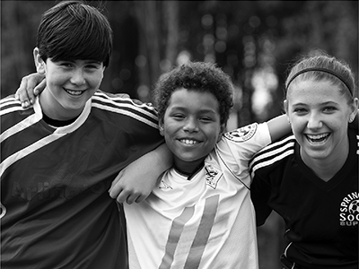 three kids in sports uniforms smiling