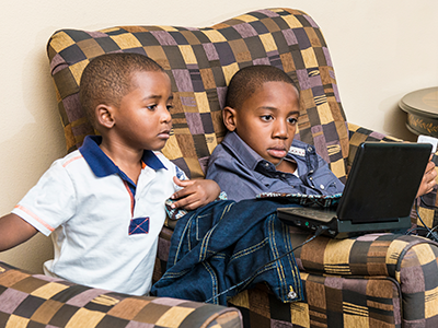 two boys looking at a computer screen