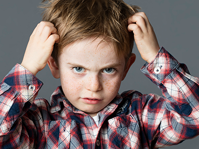 Unhappy kid scratching hair for head lice
