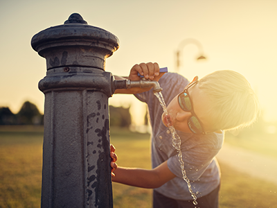 Little boy drinking water from public fountain