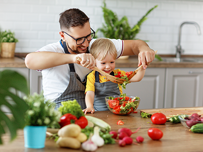 father with son preparing salad