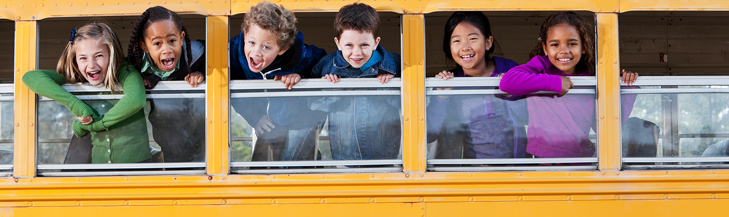 Children looking out school bus window