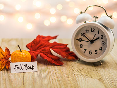 Fall Back Daylight Saving Time concept with white clock and autumn leaves