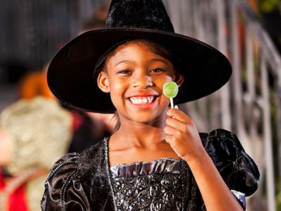 Little girl in halloween costume eating lollipop