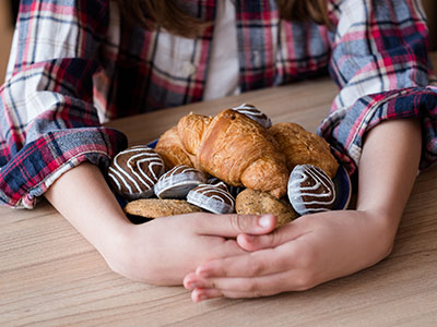 child hoarding cookies and croissants