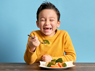 happy kid eating broccoli