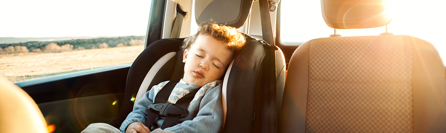 boy asleep in car seat