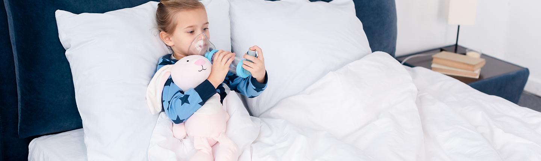 little girl in bed using an asthma inhaler