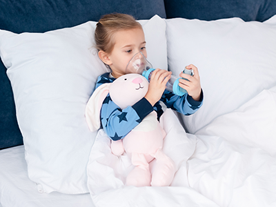 little girl in bed using an asthma inhaler
