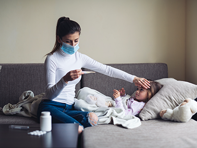 mother measuring temperature of sick child