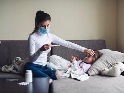 mother measuring temperature of sick child