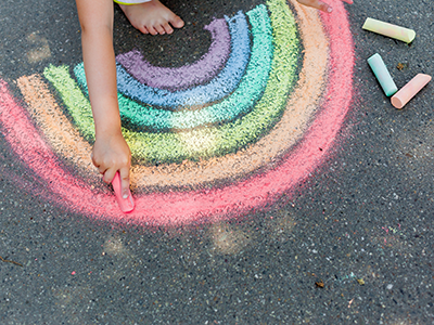 child drawing chalk rainbow