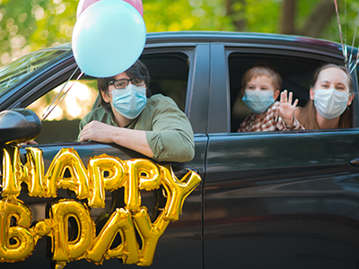 family celebrating birthday while social distancing in car