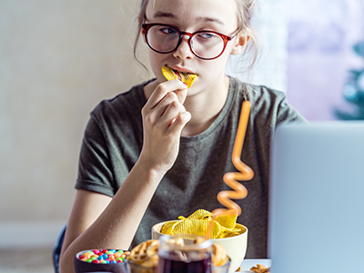 Girl working at a computer and eating fast food