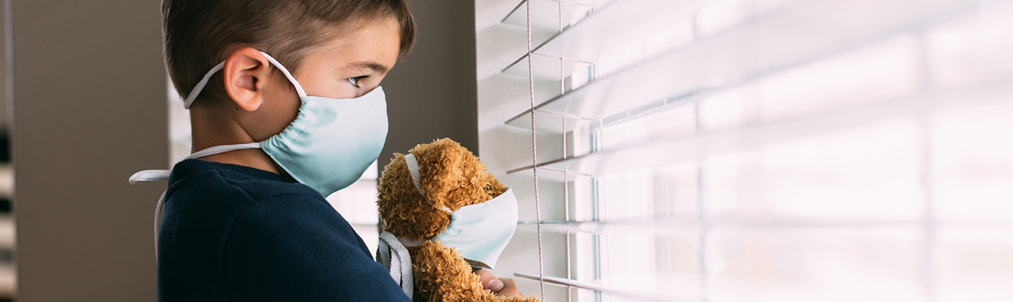 Young boy and his teddy bear wearing face masks
