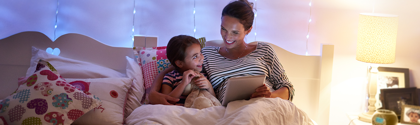 mom reading book to kid in bed