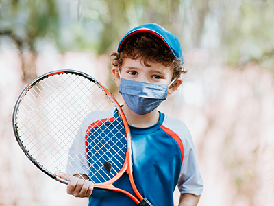 boy with tennis racket and face mask
