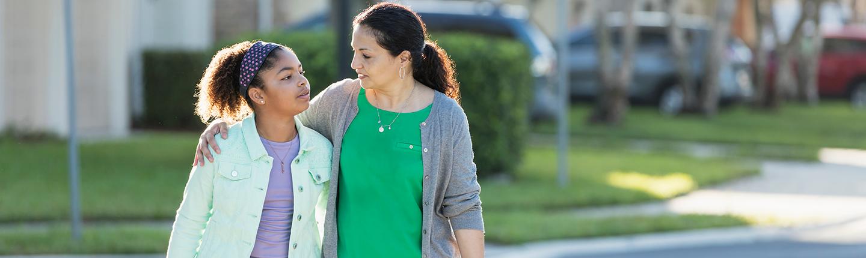 mother talking to daughter while walking