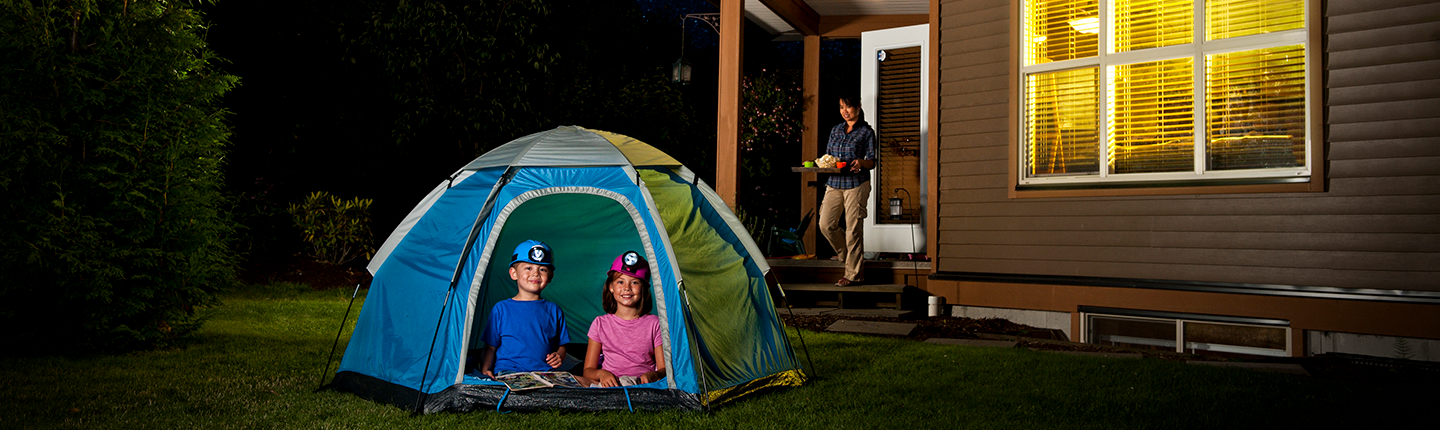 Children camping in a tent in the backyard