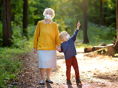 grandmother and grandchild walking through the forest
