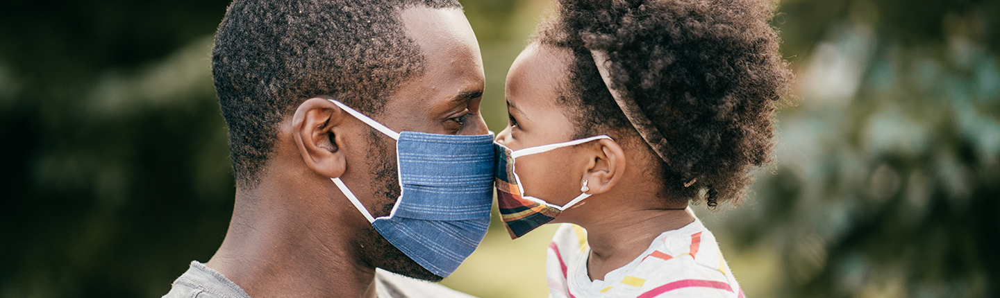 Father and toddler wearing masks