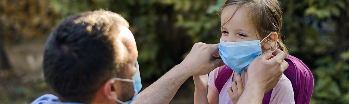 father putting mask on daughter