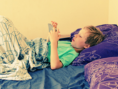 boy in bed using tablet