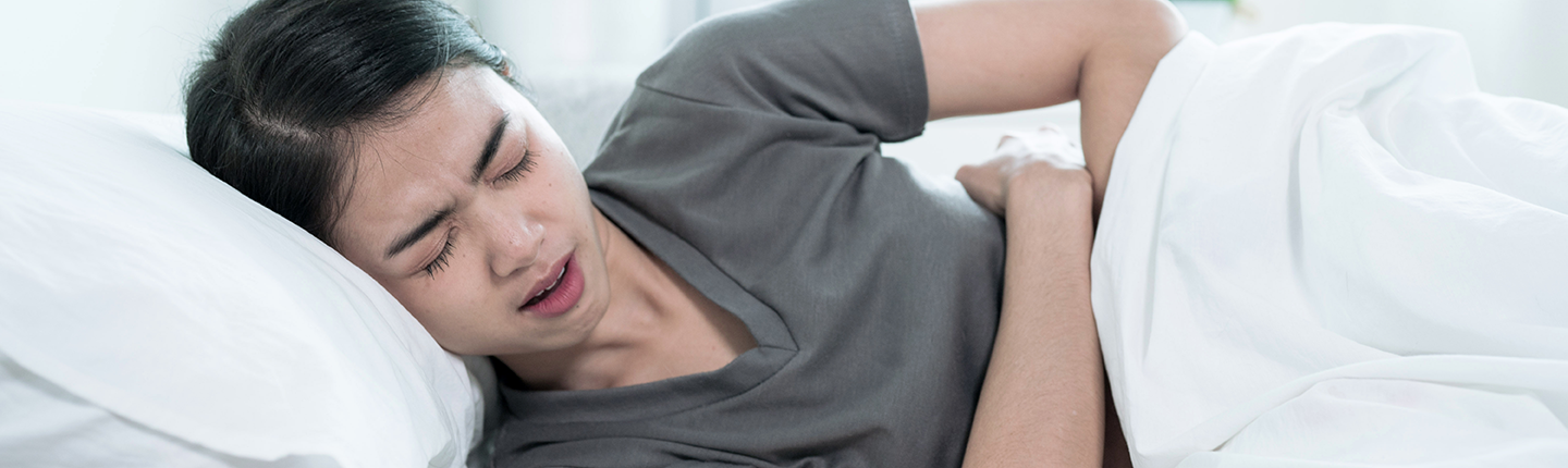girl in bed with stomach pain