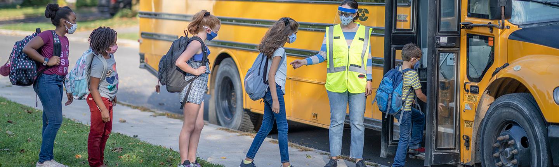 kids in masks getting on school bus