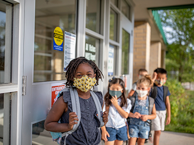 masked kids waiting in line for school