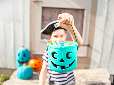 boy dressed as pirate holding a teal pumpkin